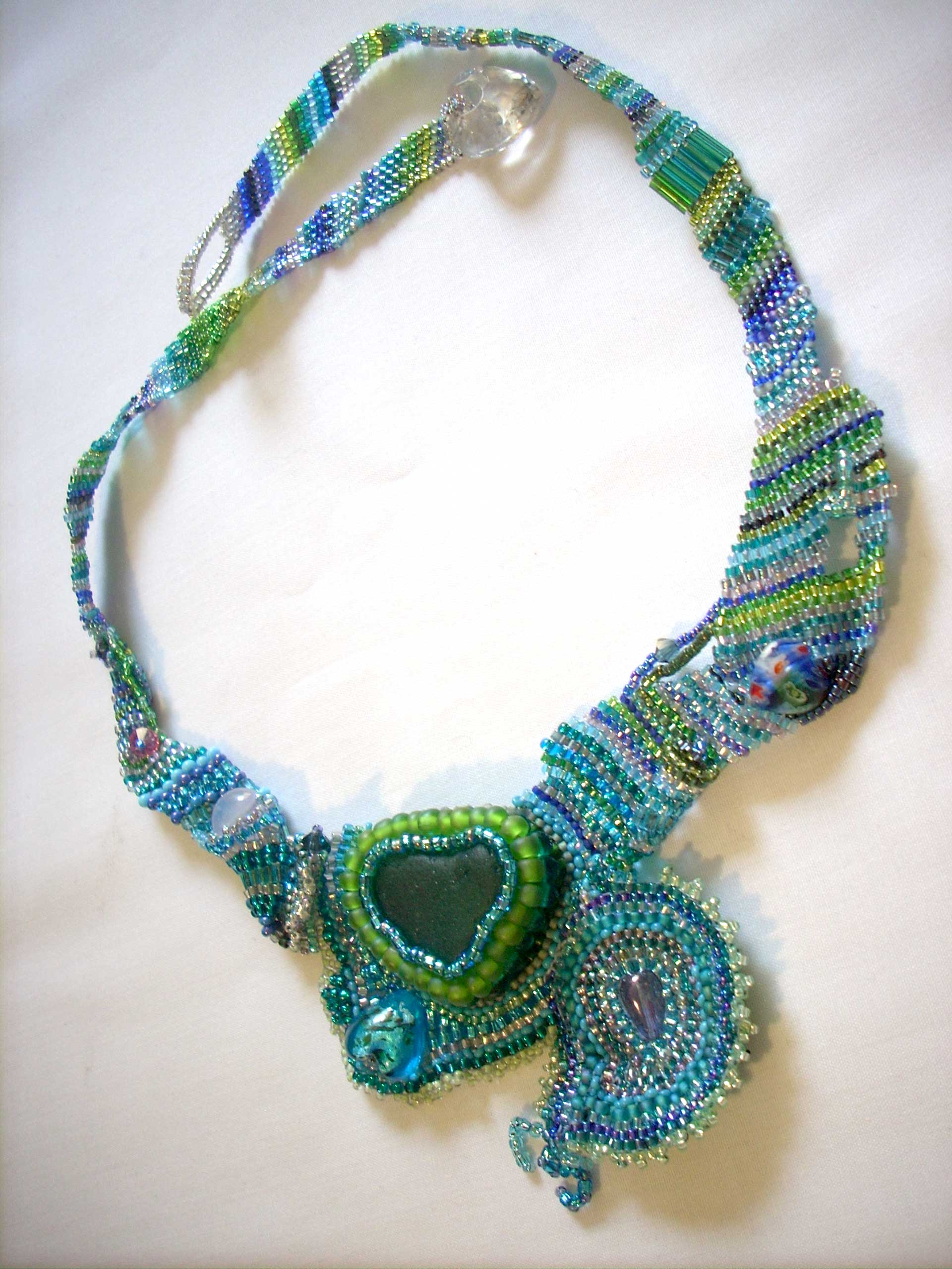 baroque handmade necklace with deep green heart of sea glass surrounded by seed beads in greens and blues